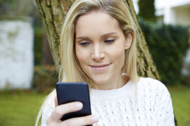 Portrait of smiling blond woman looking at cell phone outdoors - FMKF04752