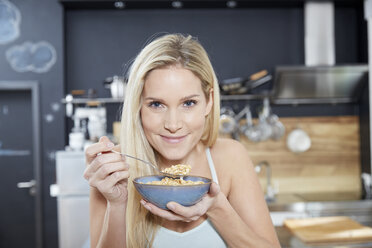 Portrait of smiling blond woman in the kitchen eating cereals - FMKF04755