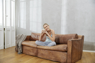 Happy woman sitting on couch with cup of coffee - FMKF04758