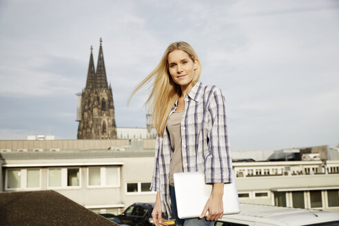 Germany, Cologne, portrait of smiling blond woman with laptop - FMKF04761