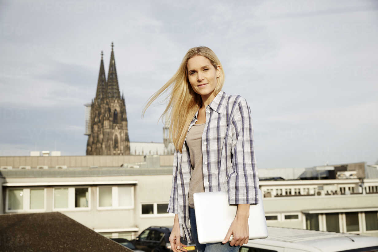 Germany, Cologne, portrait of smiling blond woman with laptop - FMKF04761 - Jo Kirchherr/Westend61