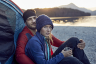 Young couple sitting at tent at lakeshore - PNEF00429