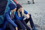 Two happy female friends sitting at tent looking at cell phone - PNEF00432