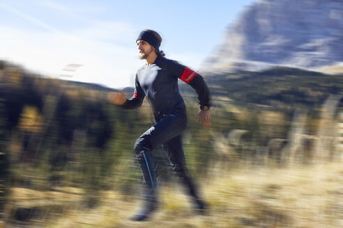 Man running fast on mountain trail - PNEF00435