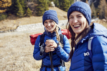 Two laughing young women hiking in the mountains - PNEF00444