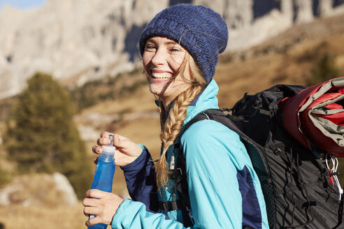 Portrait of happy young woman hiking in the mountains - PNEF00450
