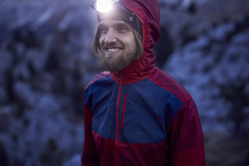 Portrait of smiling man wearing headlamp at dusk in the mountains - PNEF00459