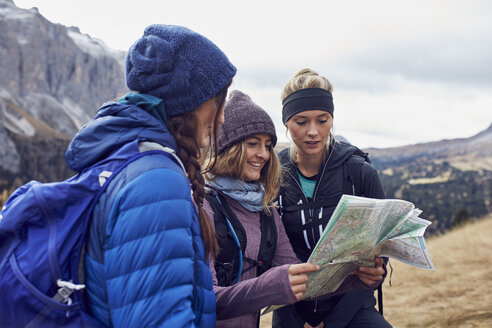 Three young women hiking in the mountains looking at map - PNEF00462