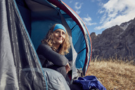 Smiling young woman sitting in tent in the mountains - PNEF00468