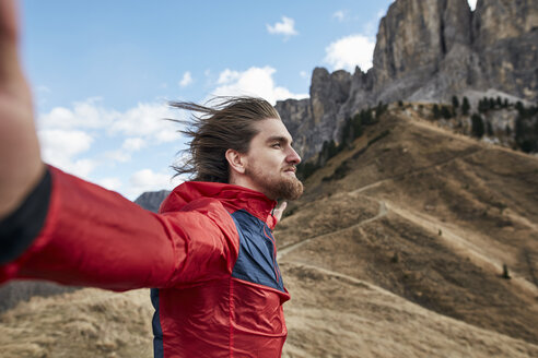 Young man leaning against the wind in the mountains - PNEF00477