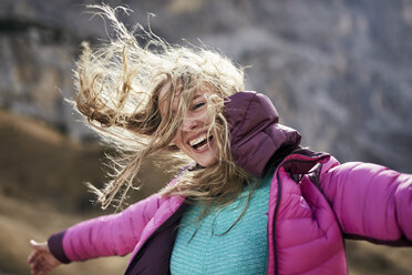 Happy young woman leaning against the wind in the mountains - PNEF00480