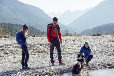 Germany, Bavaria, Karwendel, group of friends hiking with dog at the riverside - PNEF00486