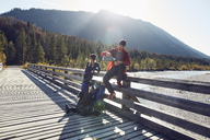 Group of friends with dog hiking resting on a bridge - PNEF00492