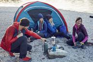 Group of hikers camping at lakeshore at sunset - PNEF00504