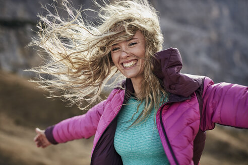Happy young woman leaning against the wind in the mountains - PNEF00507