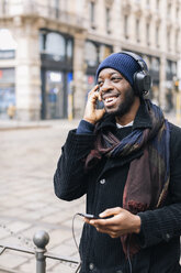 African american man with smartphone and headpone - MAUF01300