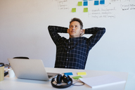 Businessman leaning back at desk in office - EBSF02090