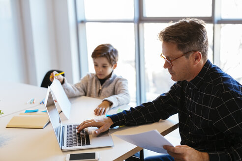 Businessman using laptop at desk in office with son sitting next to him - EBSF02096