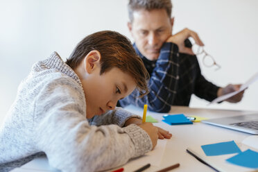 Businessman at desk in office looking at son drawing - EBSF02099