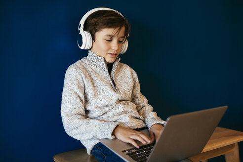 Boy sitting on bench wearing headphones and using laptop - EBSF02105