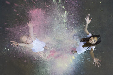 Two friends throwing colour powder in the air - PSTF00095