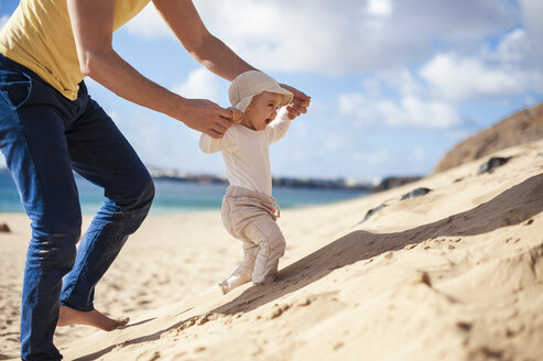 Spain, Lanzarote, baby girl walking on the beach with the help of his father - DIGF03234