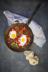 Shakshouka with chick peas in pan and slices of baguette - LVF06667