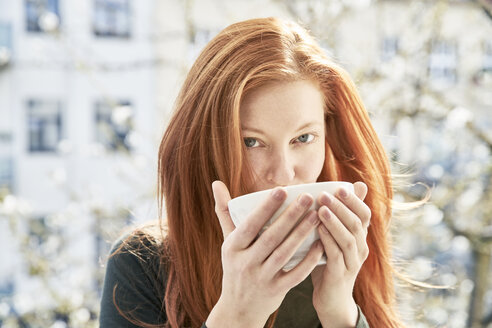 Portrait of redheaded woman drinking bowl of white coffee on balcony - FMKF04764