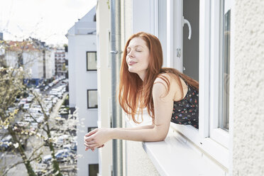 Portrait of redheaded woman with eyes closed leaning out of window - FMKF04767