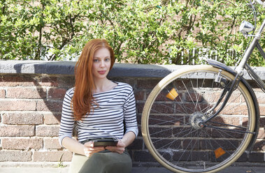 Portrait of redheaded woman with tablet and bicycle sitting on a wall - FMKF04776
