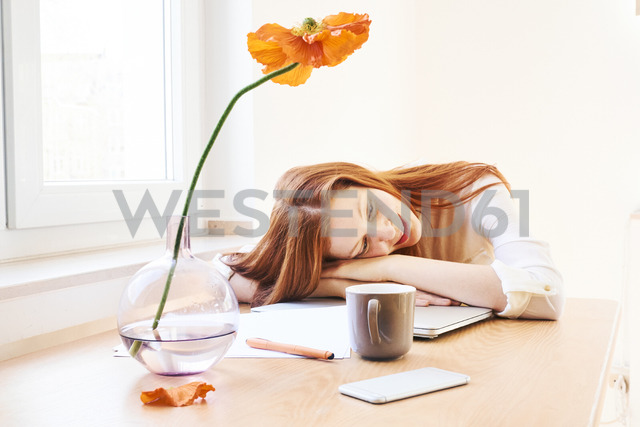 Redheaded woman at home office having a break - FMKF04779