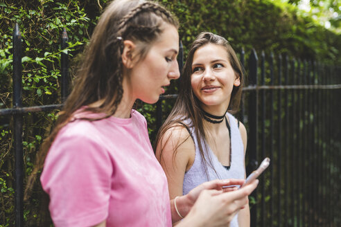 Two teenage girls with cell phone outdoors - WPEF00002