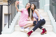 Two happy teenage girls sitting on stairs in the city taking a selfie - WPEF00008