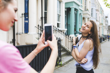 Young woman taking cell phone picture of teenage girl in the city - WPEF00011