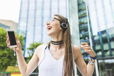 Happy teenage girl with cell phone and headphones in the city - WPEF00026