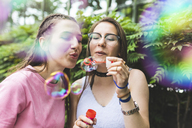 Two teenage girls blowing soap bubbles together - WPEF00032