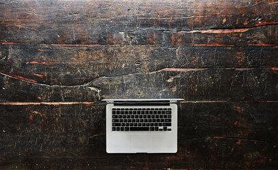 Laptop on dark wood, top view - FMKF04781