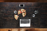 Laptop, smartphone, pizza and water glasses on tabletop, top view - FMKF04787