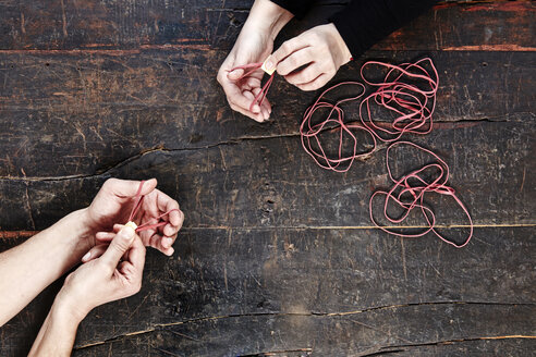 Hands of man and woman playing with rubber bands, top view - FMKF04790