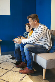 Father and son playing video game on couch at home - EBSF02114