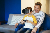 Boy wearing VR glasses playing video game with father on couch at home - EBSF02117