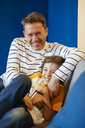 Happy father tickling son on couch at home - EBSF02123
