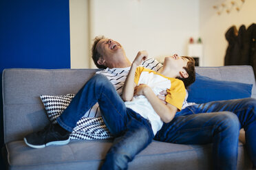 Carefree father and son having fun on couch at home - EBSF02126