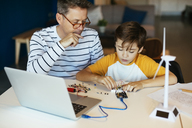 Father and son assembling a construction kit with laptop and wind turbine model - EBSF02129