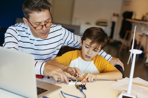 Father and son assembling a construction kit with laptop and wind turbine model - EBSF02132