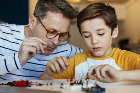 Father and son assembling an electronic construction kit - EBSF02135