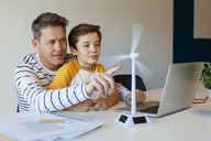 Father and son with laptop testing wind turbine model - EBSF02138