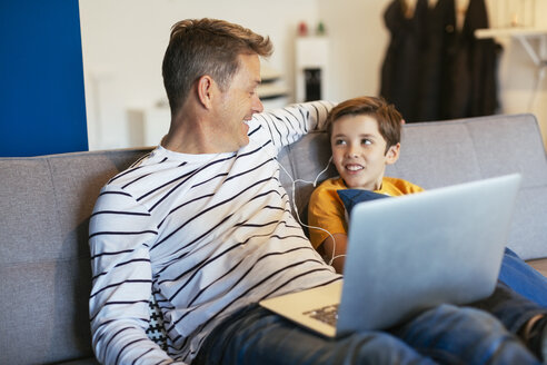 Smiling father and son with earbuds and laptop on couch at home - EBSF02141