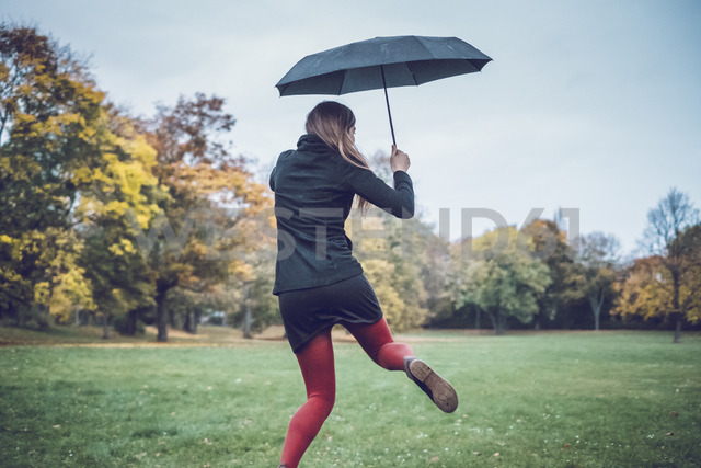 Back view of young woman with umbrella dancing in autumnal park - JSCF00028