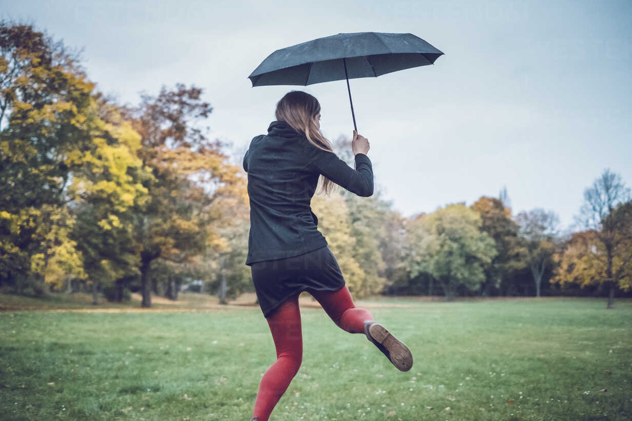 Back view of young woman with umbrella dancing in autumnal park - JSCF00028 - Jonathan Schöps/Westend61